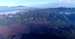 Aerial footage of lava fields at the bottom of the Batur volcano, its crater and the Batur lake. The camera is panning along the lava fields towards the lake.