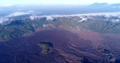 Aerial footage of lava field from Batur volcano next to the Batur lake with the Agung volcano in the background. The camera is panning from the lava field towards the lake.