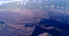 Aerial footage of lava fields at the bottom of the Batur volcano. The camera is panning along the lava fields while tilting up.