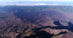 Aerial footage of lava field at the bottom of the Batur volcano. The camera is facing down at the field and is descending straight.