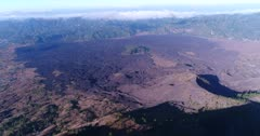 Aerial footage of lava field at the bottom of Batur volcano crater with smoke along the edge. The camera is facing down at the lava field and is panning towards the crater.