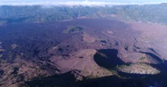 Aerial footage of lava fields at the bottom of the Batur volcano, Bratan caldera in the background. The camera is panning along the lava fields.