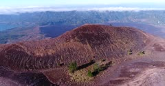Aerial footage of edge of Batur volcano crater with lava field at the bottom. The camera is going sideway along the edge.