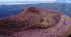 Aerial footage of edge of Batur volcano crater with lava field at the bottom. The camera is going towards the edge of the crater.