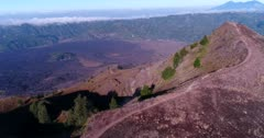 Aerial footage of edge of Batur volcano crater with lava field at the bottom. The camera is turning around the edge.