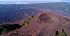Aerial footage of edge of Batur volcano crater with lava field at the bottom. The camera is going backward along the edge of the crater while descending and panning.