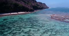 Aerial footage of shallow reef with turquoise water and some rocks slightly out of the water along remote secluded white sand beaches. The camera is going backward while panning.