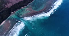 Aerial footage of shallow reef with turquoise water and a deeper channel in the middle creating rip current, waves are crashing on the outside. The camera is staying as still as possible.