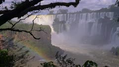 Iguazu Falls lower cataract tree silhouette and rainbow