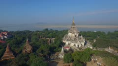 Aerial fly left by large white temple with Irrawaddy River in background