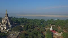 Aerial fly right by large white temple with Irrawaddy River in background
