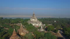 Aerial fly forward toward large white temple with Irrawaddy River in background