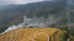 Smoke from burning straw on rice terrace