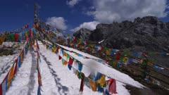 Buddhist prayer flags on snowy mountain peak