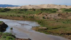 Stream with gobi desert dunes in background