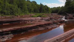 Shallow river with red rocks in the woods. Bonanza falls in Upper Peninsula. Big Iron River in the summer.