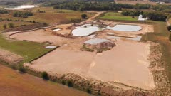 Aerial view of a sand, gravel mine quarry full with water.