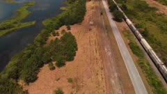 Aerial of railroad with a cargo train , country road and lakes