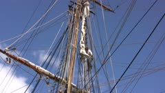 Tall Masted Sailing Ship, Crew Member Unfurling Sail