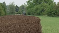 farmer in tractor plowing field