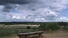 Dark clouds above a vacant wooden bench at an outlook in Veluwe National Park, a nature reserve of woods, heaths, grassy planes and drifting sands. VELUWE, THE NETHERLANDS - JULY 2015: