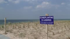Sign in dunes - no trespassing, dune plants in growth (in Dutch: duinbeplanting in aangroei, verboden toegang). Reinforced Dutch coastline.