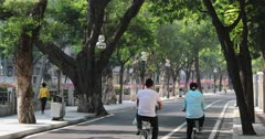 People cycling along road in Dongshan area, Guangzhou, Guangdong, China, Asia