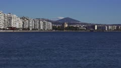 Old waterfront on left and new waterfront to right of landmark, with traffic on a sunny day, viewed from the city port area with the White Tower visible in the centre, Thessaloniki, Greece, Europe