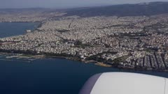 Aerial city day view taken from inside of inclining aircraft taking off from SKG international airport, Thessaloniki, Greece, Europe
