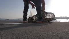 Fisherman using lobster trap on wharf in Fira, Santorini, Greece, Europe