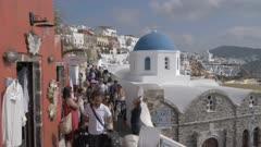 Tourists on path in village of Oia, Santorini, Greece, Europe