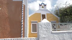 Greek flag outside brown and white church in Oia, Santorini, Greece, Europe