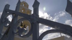 Sun through bell tower of Saint George church in Oia, Santorini, Greece, Europe