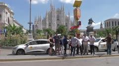 People waiting at tram stop by Duomo di Milano in Milan, Italy, Europe