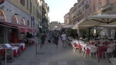 Pedestrians on street by restaurant in Milan, Italy, Europe