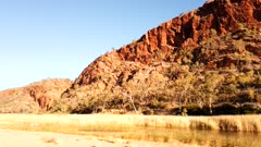 Time lapse of Glen Helen Gorge changing colours at sunset on permanent waterhole, West MacDonnell Ranges, rock formation along Red Center Way, Northern Territory, Australia, Pacific
