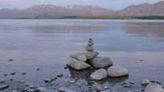 Zen stone at the Lake Tekapo with reflection the Mount John at background.