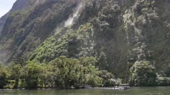 A boat at the green scenery of Milford Sound, South Island