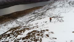 Mountaineer Walking Through Deep Snow During Ascent on a Mountain