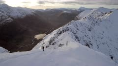 Mountain Climber Reaching the Summit of a Snowy Mountain