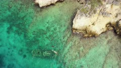 Aerial view over the island of Curaçao / Caribbean Sea with wrecked Tugboat, turquoise water, cliff, beach and beautiful coral reef