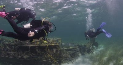 Divers Swim On Shipwreck