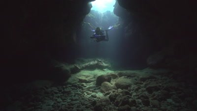 Diver approaching camera in lava tube under sky light