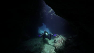 Diver swimming away through cavern under light rays