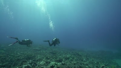 Diver pair enters frame, swims over coral reef under light rays toward deep