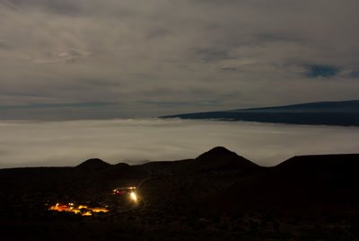 Cloud layers passing under Mauna Kea summit with town lights, timelapse