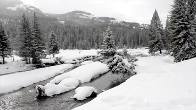 Dolly shot over, rippling river in snow covered Lamar Valley, Yellowstone N.P.