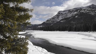 Dolly shot over river rippling through Lamar Valley in snowcovered mountains