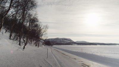 Winter in Kirkenes,Northern Norway,near Russian border. Blue VW van passes L-R