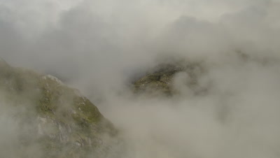 Fly over cloud covered ridge to reveal high altitude lake with waterfall in background